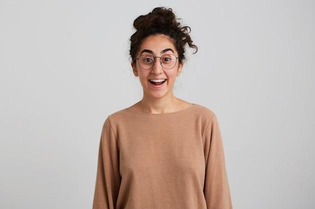 Portret van aantrekkelijk, verrast meisje met donker krullend haarbroodje, beige trui en glazen dragen