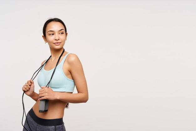 Portret van aantrekkelijk, volwassen aziatisch meisje met donker lang haar. sportkleding dragen en een springtouw om haar nek houden. kijken met belangstelling naar rechts op kopieerruimte geïsoleerd op witte achtergrond