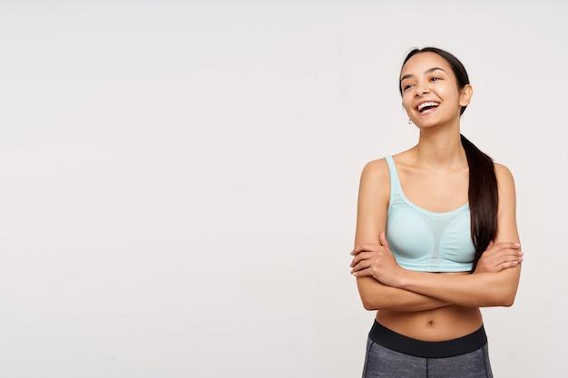 Portret van aantrekkelijk, volwassen aziatisch meisje met donker lang haar. sportkleding dragen en lachen met gekruiste armen op een borst. kijken naar links op kopieerruimte, geïsoleerd op witte achtergrond