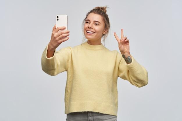 Portret van aantrekkelijk, volwassen meisje met blond haar dat in broodje en tatoegering wordt verzameld. gele trui dragen en een smartphone vasthouden. selfie maken. vredesteken tonen. tribune geïsoleerd over witte muur