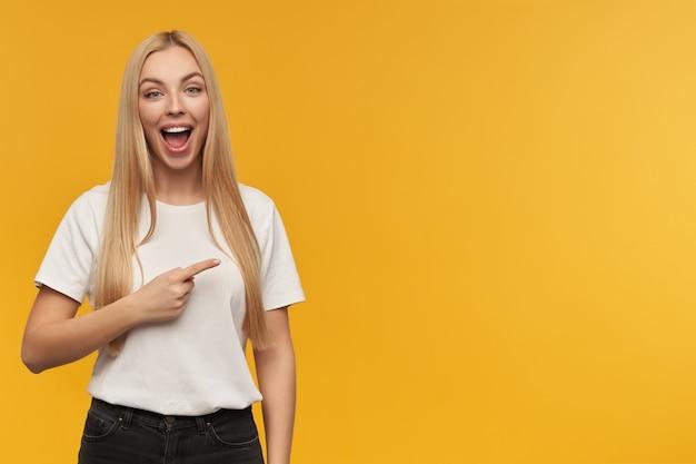 Portret van aantrekkelijk, volwassen meisje met blond lang haar. witte t-shirt en zwarte spijkerbroek dragen. kijkend naar de camera en naar rechts wijzend op kopie ruimte, geïsoleerd op oranje achtergrond