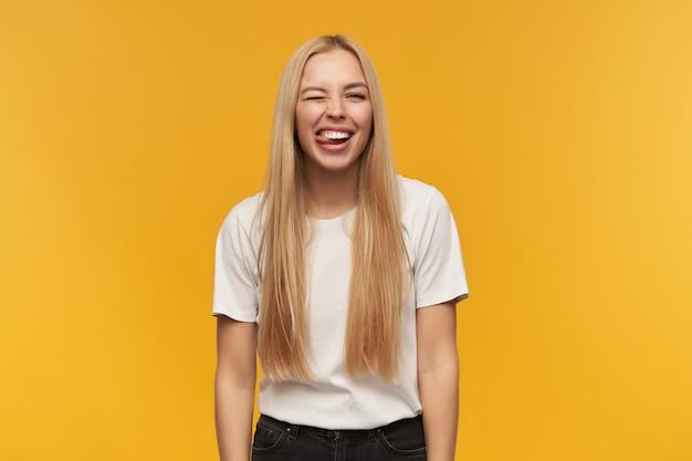 Portret van aantrekkelijk, volwassen meisje met blond lang haar. witte t-shirt en zwarte spijkerbroek dragen. mensen en emotie concept. kijken naar de camera, geïsoleerd op oranje achtergrond