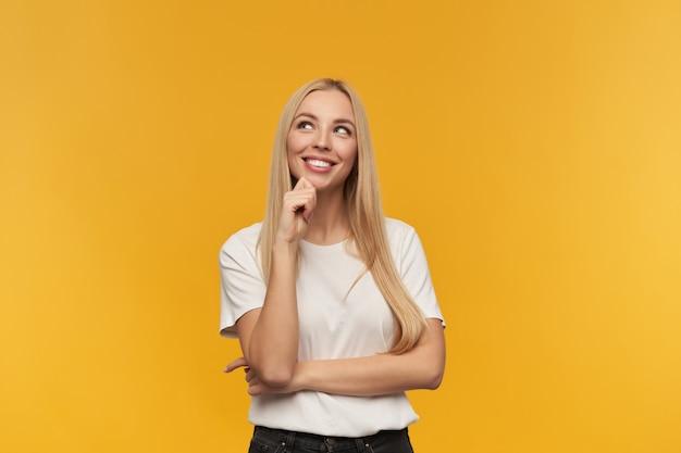 Portret van aantrekkelijk, volwassen meisje met blond lang haar. witte t-shirt en zwarte spijkerbroek dragen. mensen en emotie concept. kijken naar kopie ruimte, geïsoleerd op oranje achtergrond