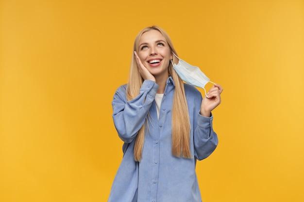 Portret van aantrekkelijk, volwassen meisje met blond lang haar. zet haar medische gezichtsmasker af. mensen en emotie concept. kijken naar de camera, geïsoleerd op oranje achtergrond
