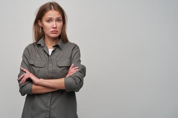 Portret van aantrekkelijk, volwassen meisje met bruin lang haar. grijs shirt dragen en armen gekruist op een borst houden. kijk verdrietig naar de camera, kopieer de ruimte aan de rechterkant, geïsoleerd over grijze achtergrond