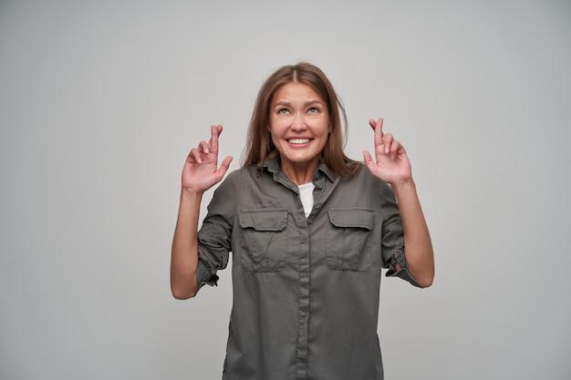 Portret van aantrekkelijk, volwassen meisje met bruin lang haar. het dragen van grijs shirt en houden haar vingers gekruist. binnen verleiding. kijken naar kopieerruimte, geïsoleerd over grijze achtergrond