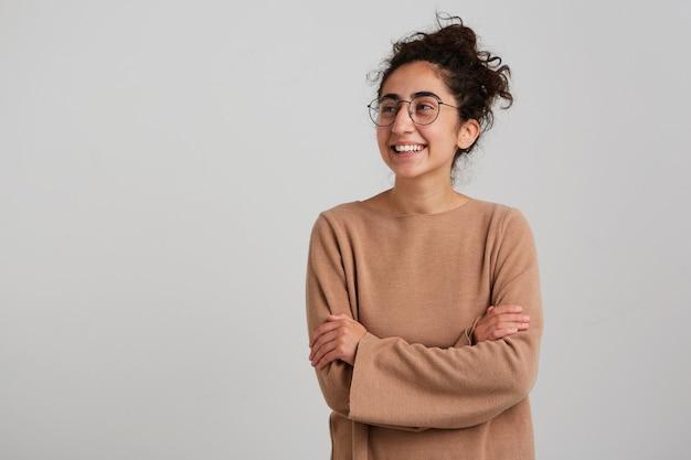 Portret van aantrekkelijk, volwassen meisje met donker krullend haarbroodje, beige trui en bril dragen