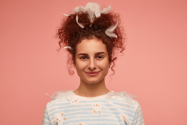 Portret van aantrekkelijk, volwassen meisje met gember krullend haar. het dragen van gestreepte trui met konijntjes en bedekt met veren, glimlachend. geïsoleerd, close-up over pastelroze muur