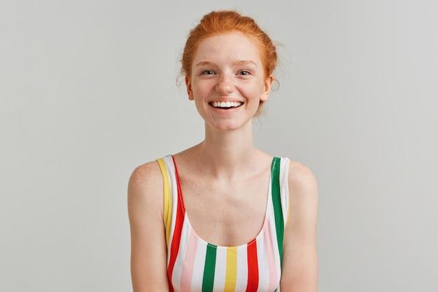 Portret van aantrekkelijk, volwassen meisje met het broodje van het gemberhaar en sproeten, gestreept kleurrijk zwempak