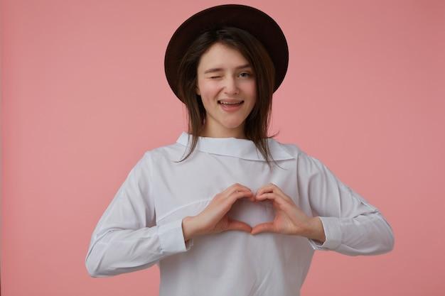 Portret van aantrekkelijk, volwassen meisje met lang donkerbruin haar. het dragen van witte blouse en zwarte hoed. liefde teken tonen. emotie concept. kijken en knipogen geïsoleerd over pastelroze muur