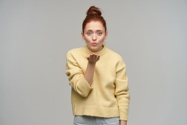 Portret van aantrekkelijk, volwassen roodharigemeisje met haar dat in een knotje wordt verzameld. pastelkleurige gele trui en spijkerbroek aan. luchtkus verzenden. geïsoleerd over grijze muur