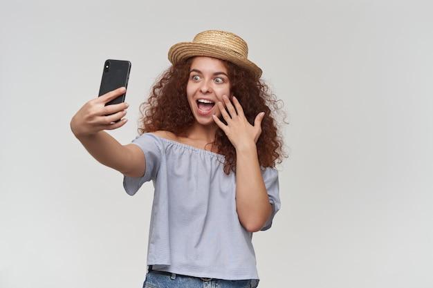 Portret van aantrekkelijk, volwassen roodharigemeisje met krullend haar. gestreepte blouse en hoed met blote schouders. een selfie maken op een smartphone en haar gezicht aanraken. tribune geïsoleerd over witte muur