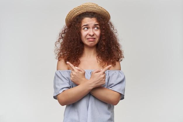 Portret van aantrekkelijk, volwassen roodharigemeisje met krullend haar. gestreepte blouse en hoed met blote schouders. kijkend naar rechts op kopie ruimte en naar beide kanten wijzend, geïsoleerd over oranje muur