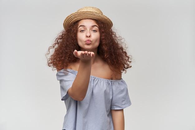 Portret van aantrekkelijk, volwassen roodharigemeisje met krullend haar. gestreepte blouse en hoed met blote schouders. luchtkus verzenden. geïsoleerd over witte muur