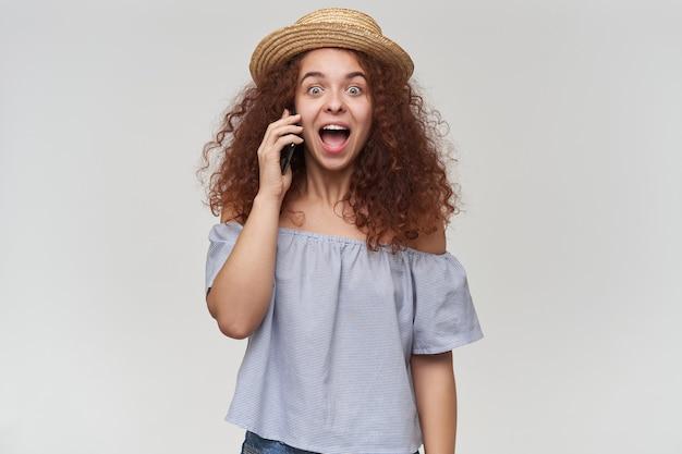 Portret van aantrekkelijk, volwassen roodharigemeisje met krullend haar. gestreepte blouse en hoed met blote schouders. praat via een telefoon, luister naar goed nieuws. geïsoleerd over witte muur