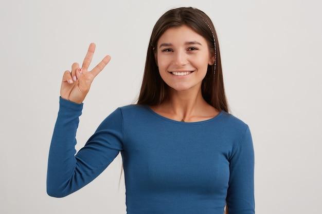 Portret van aantrekkelijk, vrolijk meisje met donker lang haar, gekleed in een blauwe trui