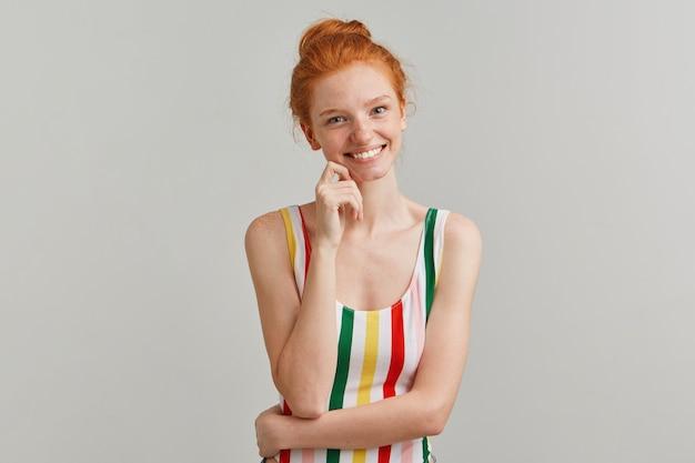 Portret van aantrekkelijk, vrolijk meisje met gember haarbroodje en sproeten, gestreepte kleurrijke zwembroek dragen