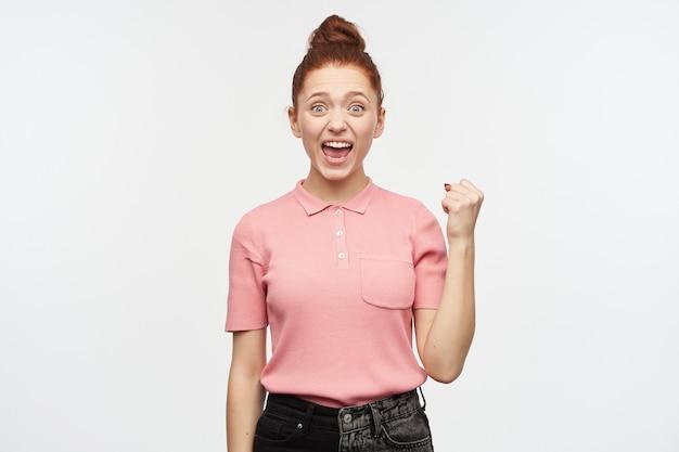 Portret van aantrekkelijk, vrolijk meisje met het broodje van het gemberhaar.