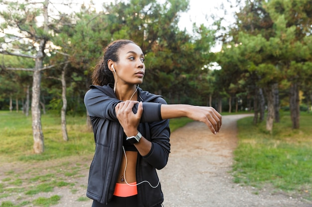 Portret van aantrekkelijke afrikaanse amerikaanse vrouwen20s die zwart trainingspak dragen die oefeningen doen, en haar lichaam in groen park uitrekken