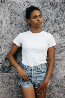 Portret van aantrekkelijke afro-amerikaanse vrouw op korte broek en t-shorts op grijze muur