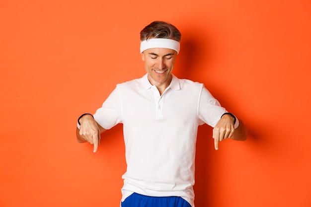 Portret van aantrekkelijke atletische kerel van middelbare leeftijd, wijzende vingers naar beneden