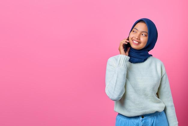 Portret van aantrekkelijke aziatische vrouw die op smartphone praat en er gelukkig uitziet
