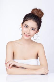 Portret van aantrekkelijke aziatische vrouwenzitting die op witte achtergrond glimlachen.