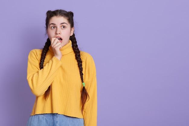 Portret van aantrekkelijke bang jonge vrouw met twee vlechten bijten vuist