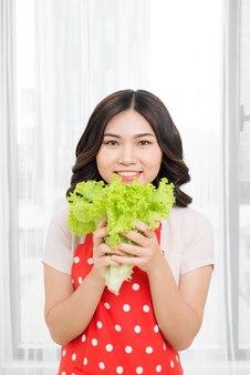 Portret van aantrekkelijke blanke lachende vrouw geïsoleerd op keuken schot eten salat
