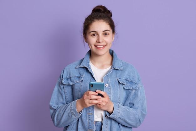 Portret van aantrekkelijke blanke vrouw draagt een stijlvolle spijkerjasje, staand binnen tegen lila muur met moderne smartphone in handen,