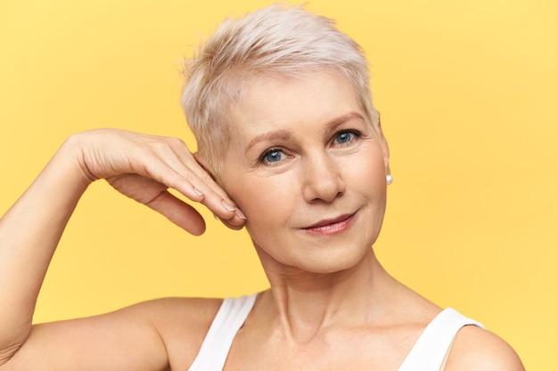 Portret van aantrekkelijke blanke vrouw van middelbare leeftijd in tank top aanraken wang, toepassing van anti rimpel vochtinbrengende crème, camera kijken met een glimlach.