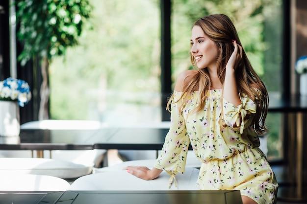 Portret van aantrekkelijke blonde blanke vrouw, model, luncht op het terras van het café en kijkt ernaar uit
