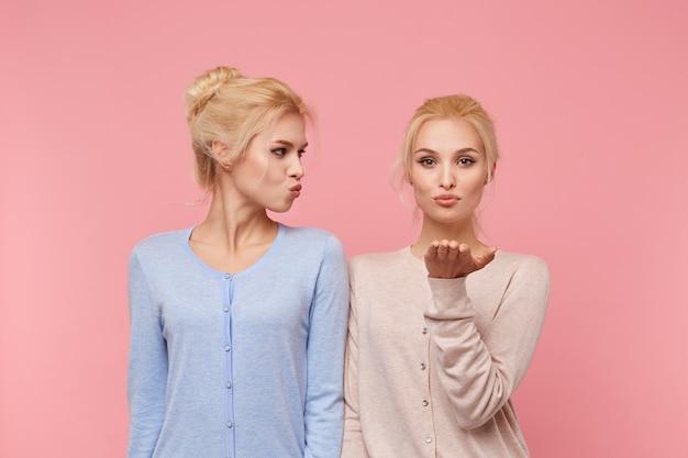 Portret van aantrekkelijke blonde jonge tweelingzusjes, luchtkusjes verzenden, liefde betuigt aan iemand op afstand, staat op roze achtergrond.