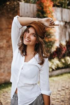 Portret van aantrekkelijke bruinogige jonge vrouw in oversized katoenen overhemd en corduroy hoed met glimlach die camera in tuin bekijkt.