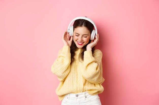 Portret van aantrekkelijke brunette meisje genieten van muziek luisteren, dansen en glimlachen tevreden, staande tegen roze muur. kopieer ruimte