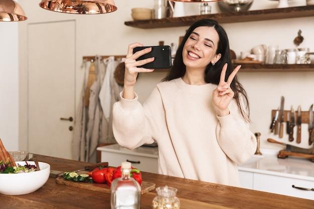Portret van aantrekkelijke brunette vrouw selfie foto nemen op smartphone tijdens het koken van groene salade met groenten in stijlvolle keuken thuis