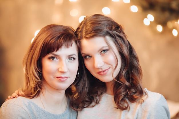 Portret van aantrekkelijke dochter en haar moeder in pasteltinten met make-up en kapsels