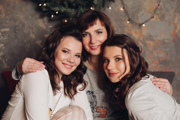 Portret van aantrekkelijke dochters en hun moeder in pasteltinten met make-up en kapsels