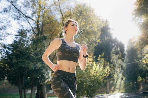 Portret van aantrekkelijke donkerbruine vrouwelijke agent die in oortelefoons van de stadspark airpods bluetooth hoofdtelefoons lopen. gezonde fitness atletische vrouw joggen buitenshuis