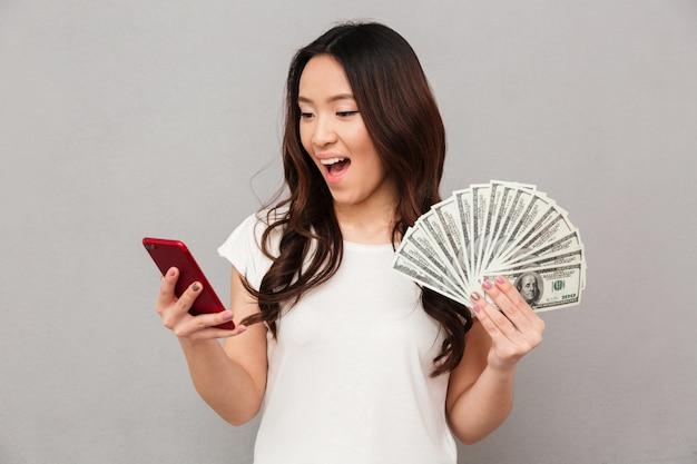 Portret van aantrekkelijke donkerbruine vrouwelijke jaren '20 die veel munt van de gelddollar winnen die haar smartphone gebruiken, dat over grijze muur wordt geïsoleerd