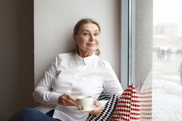 Portret van aantrekkelijke elegante volwassen blanke vrouw in wit overhemd ontspannen in koffiehuis met mok cappuccino, zittend op de vensterbank en gelukkig glimlachen. mensen en levensstijlconcept