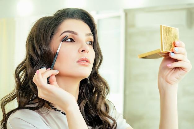 Portret van aantrekkelijke en mooie vrouw visagiste visagiste zit voor een spiegel en past oogschaduw cosmetica make-up op het gezicht in salon studio. concept van zelfzorg en zelfliefde