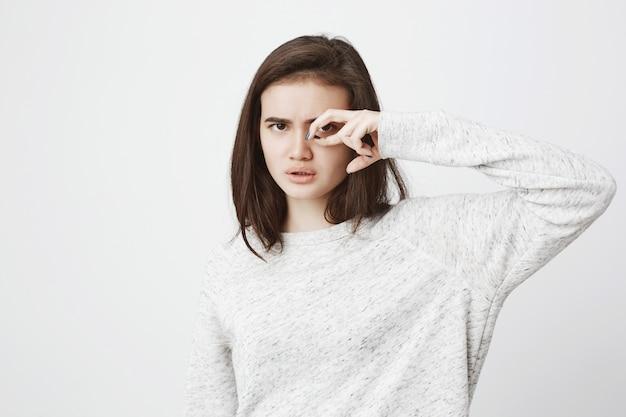 Portret van aantrekkelijke ernstig ogende vrouw in witte sweater die gebaar dichtbij oog met geconcentreerde en zekere uitdrukking maakt.