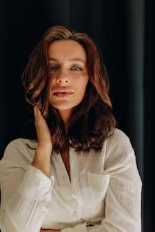 Portret van aantrekkelijke europese vrouw met donker golvend haar en blauwe ogen poseren aan haar gezicht te raken