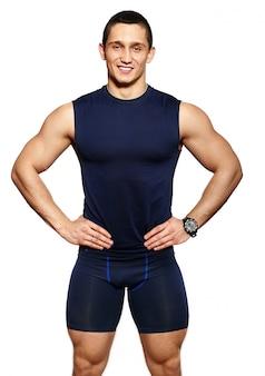 Portret van aantrekkelijke fitness gezonde lachende gelukkig vrolijke man in sportkleding op wit wordt geïsoleerd