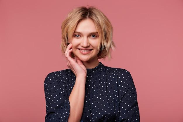 Portret van aantrekkelijke flirterige jonge mooie blonde met kort kapsel hand in de buurt van het gezicht, gekleed in blouse met stippen, jassen, flirten, aangenaam glimlachen, geïsoleerd over roze muur