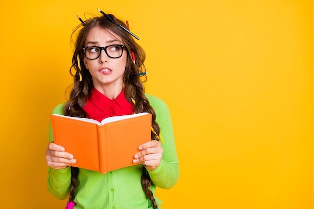 Portret van aantrekkelijke funky nerveuze tienermeisje lezen werkboek denken bijten lip kopie ruimte geïsoleerd over heldere gele kleur achtergrond