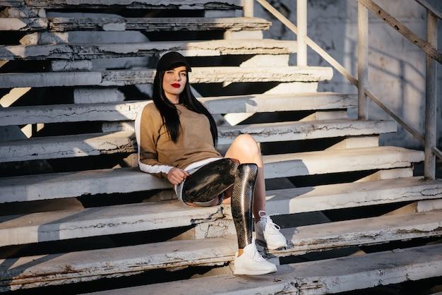 Portret van aantrekkelijke gehandicapte vrouw in zwarte trainingspak met prothetisch been