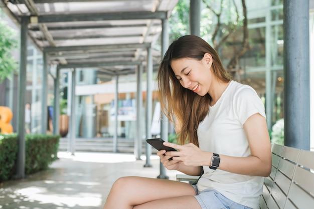 Portret van aantrekkelijke gelukkige aziatische smartphone van de vrouwenholding terwijl het zitten op kant van de weg bij de stad