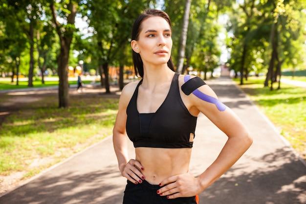 Portret van aantrekkelijke gespierde brunette vrouw, gekleed in zwarte sport outfit, camera kijken